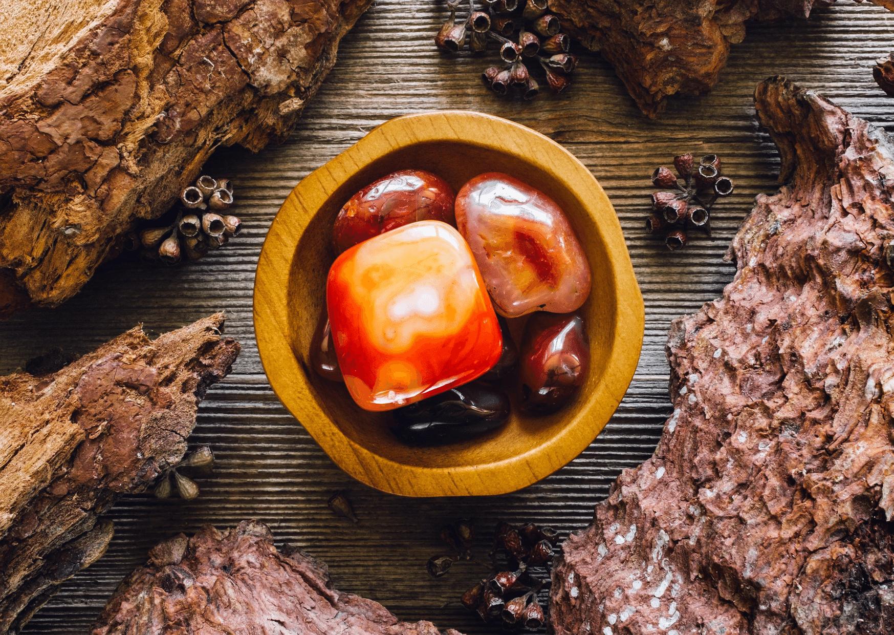 pierres cornaline dans bol marron entouré de bois