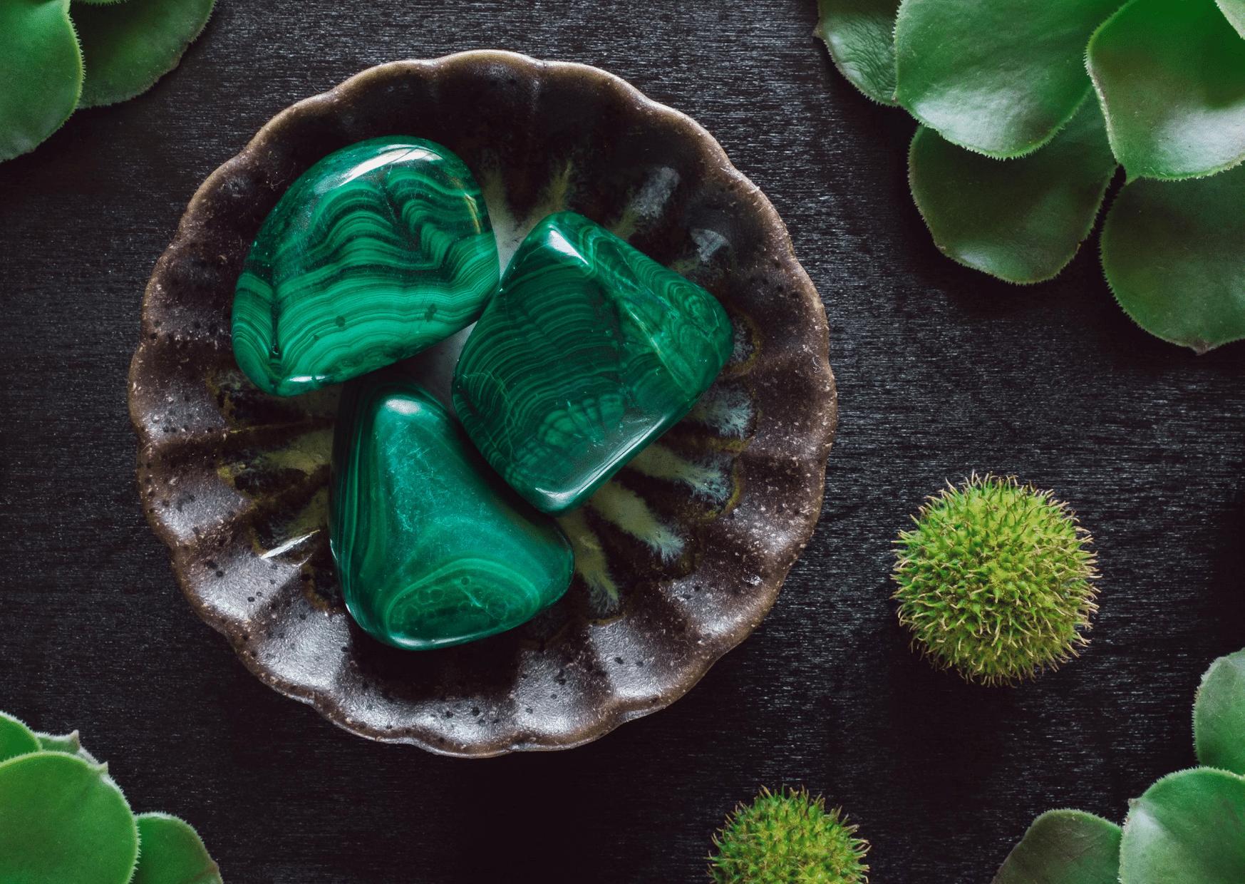 pierres malachite dans bol marron entouré de feuilles pierre verte
